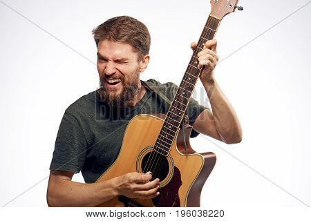 Young guy with a beard on a white isolated background holds a guitar.