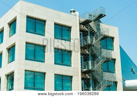 Fire escape ladder stairs on modern building exterior wall.