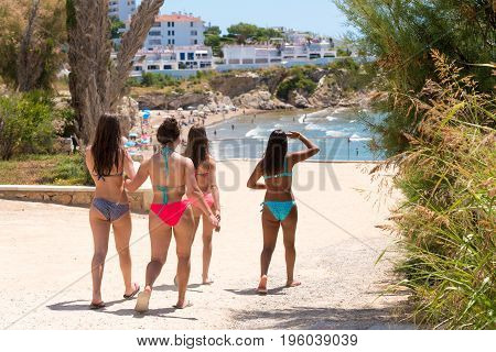 Four Girls In Bathing Suits Go To The Beach In Sitges, Barcelona, Catalunya, Spain.