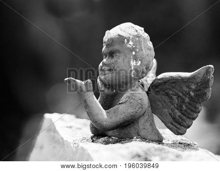 an angel on a stone providing his hand