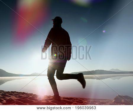 Leakage Of Light In The Lens.  Exercising  Man Silhouette On Beach Against To Morning Sun.