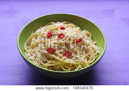 spaghetti with cheese and peppers in a green bowl on a lilac background