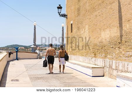 Two Men Go Through The Historic Center In Sitges, Barcelona, Catalunya, Spain. Copy Space For Text.