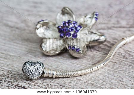 Jewelry for women silver bracelet and brooch flower modern fashion amulets precious products macro retro style selective focus
