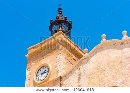 View Of The Church Tower With Clock In Sitges, Barcelona, Catalunya, Spain. Isolated On Blue Backgro