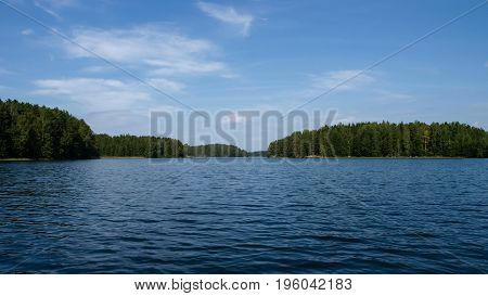 Finnish lake on a clear summer day with lush green islands and coasts