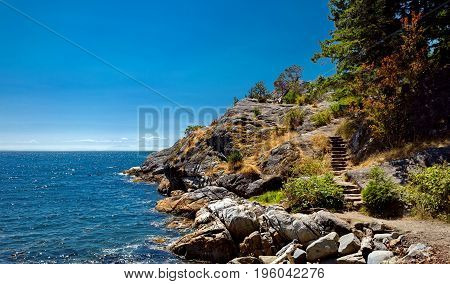 Cliff and rocky beach in the  Strait of Georgia British Columbia,  coastline and forest.