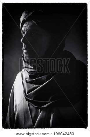 Vintage Black And White Profile Photo Of Berber Man In Night Light Wearing Turban With Robe. Studio