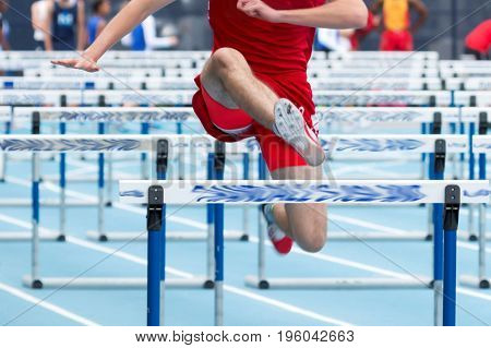 A male high school hurdler competes in the 110 meter high hurdles wearing a red uniform on a blue track