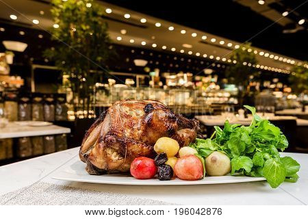 Garnished roasted turkey on platter on marble surface served with herbs