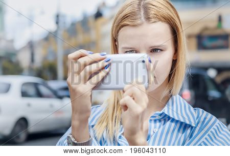 Girl in striped shirt, uses mobile flashlight, on a cloudy day, outdoor. Teenager takes pictures on smartphone, holding it with both hands, on the background of houses.Looks attentively at the screen
