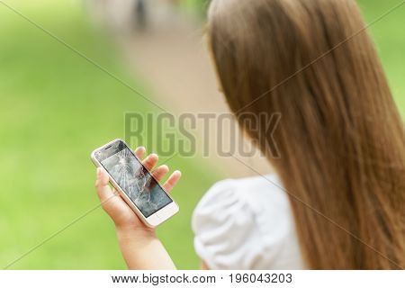 Little Girl In Desperation Is Holding A Phone With A Broken Screen