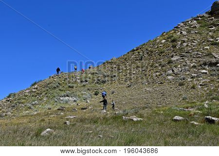 Unidentified hikers climb a rocky butte in the prairies of South Dakota