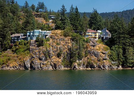 A village on the cliff in the  Strait of Georgia in West Vancouver  British Columbia, a coastline and a forest.