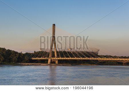 Modern bridge in Warsaw over Vistula river during sunset Poland