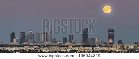 Panorama of rising moon over Warsaw city in summer time