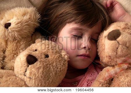 Una joven toma una siesta con sus osos de peluche