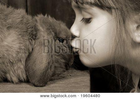 A young girl giving her bunny kisses