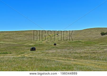 A winding prairie trail in a remote region finds three vehicles traveling in the remote barren region