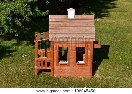 A child`s backyard play house with a porch, stove, sink and chimney.