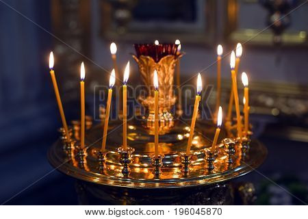 burning yellow candles in the Church, standing on a pedestal