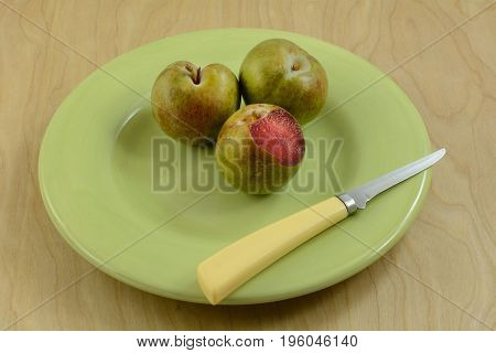 Plum apricot hybrid plums in green plate with knife on wooden table