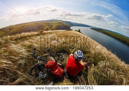 Mountain bike adventur. Cyclist has a rest on riverside. Healthy life concept.