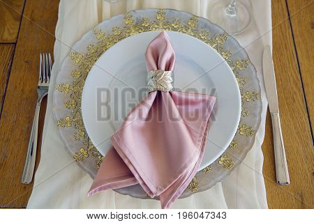 festive table decoration at the wedding in the form of plates and pink cloth