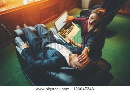 Scene from office life: businesswoman is showing her male boss information on screen of laptop but her colleague is chilling in black leather reclining massage chair and covering his face with palm