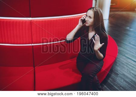 Beautiful caucasian business lady having phone conversation with her friend and emotionally gesticulates while sitting on red sofa in office chillout with copy space for logo text or your advertising