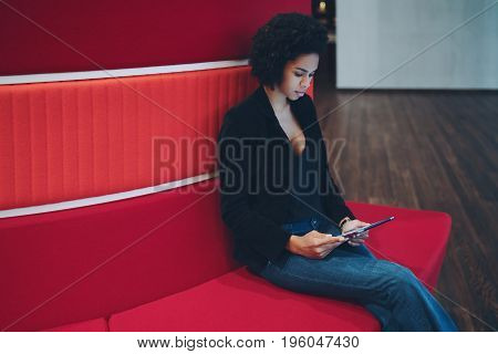 Cute curly afro american student girl with curly hair is sitting on red sofa while waiting her lesson start and watching movie using digital tablet with copy space for text your advertise or logo