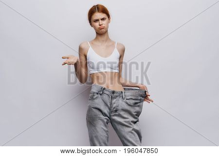 Young beautiful woman on a light background, losing weight, diet, sports, fitness.