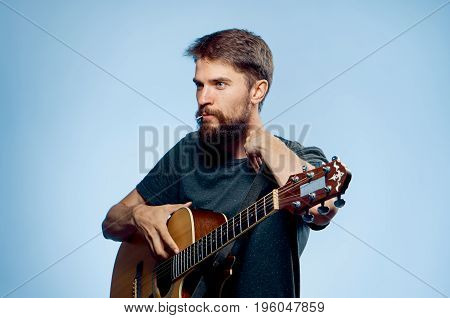 Young guy with a beard on a blue background holds a guitar.