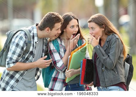 Three gossip students telling secrets in the street