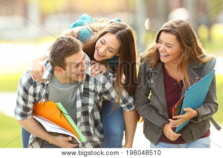Three happy students and friends joking and laughing together in an university campus with a green background