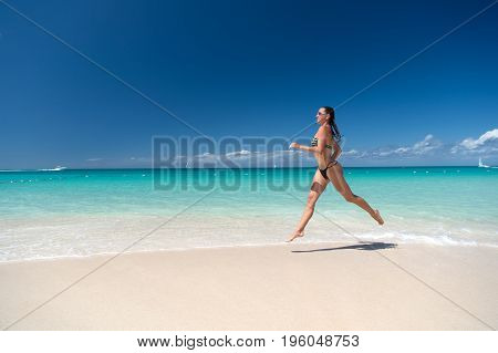 Woman in swimsuit running on sea beach with white sand turquoise water and blue sky on sunny day on natural environment. Sun tanning bathing. Summer vacation. Rest relaxing active leisure