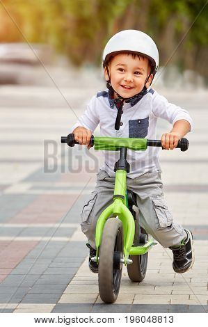Happy boy in white helmet ride his first bike in city park