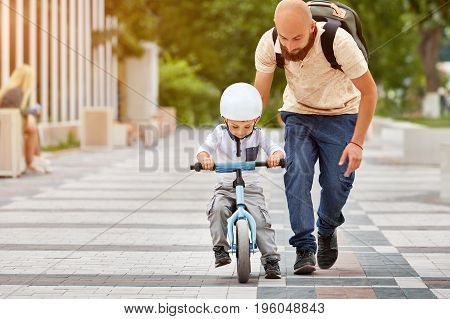 Father help his son ride a bicycle in city park
