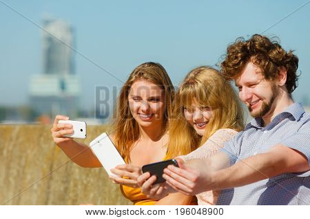 Friends taking selfie self photo picture with smartphone. Young women and man having fun outdoor. Summer relax.