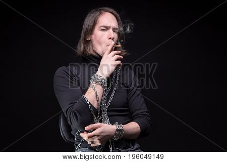 Smoking young man and shackles on black background