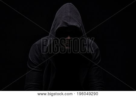 Young man in hood and shadow on black background