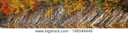 Rocky shore of lake in autumn time. colored wood