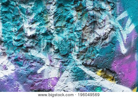 Dirty city wall, spattered with colorful patches of bright colors aerosols. Modern iconic urban culture, stylish pattern, fashion colors