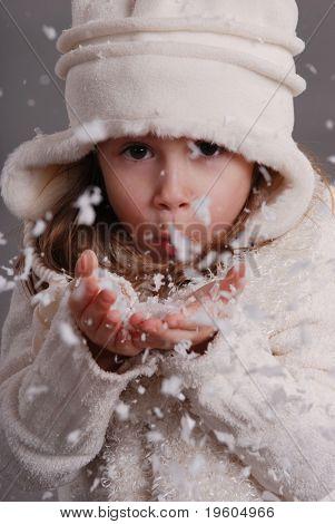 Een schattig jong meisje waait sneeuw