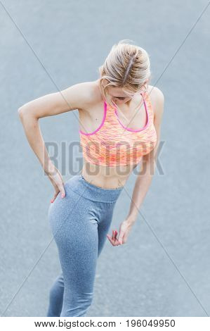 healthcare and medicine concept - close up of sporty woman touching her back. Young woman in sportswear touching her lower back muscles by painful injury. Young athletic woman suffering back pain