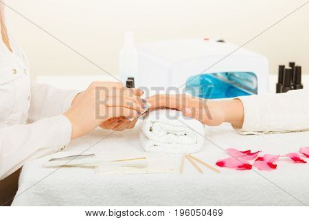Woman hand on towel preparing gel hybrid manicure using nail polish remover to remove dust and oil from nails. Beauty wellness spa treatment concept