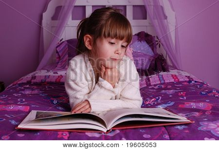 A cute young girl lying on her bed reading a book