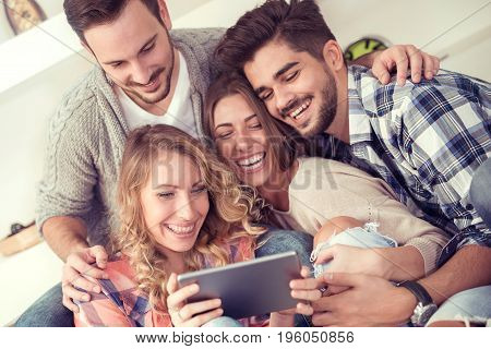 Group of friends taking a selfie on a tablet and smiling.
