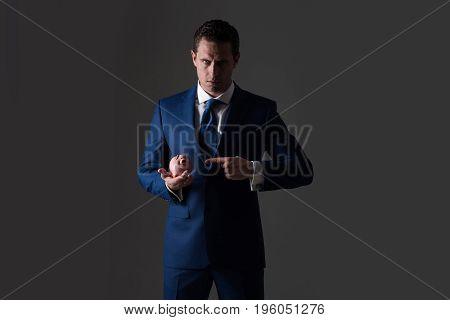 Elegant Man Pointing At Piggy Bank