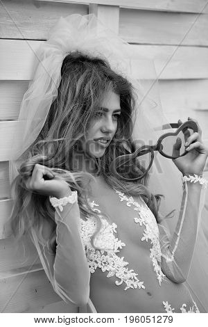 girl with long hair in wedding dress and bride veil holding glasses in heart shape on wooden background black and white